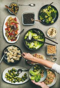 Healthy vegan dishes and woman hand taking cauliflower from plate