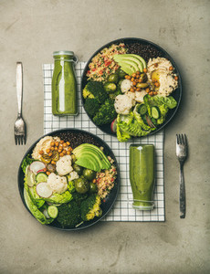 Flat lay of healthy dinner with superbowls and green smoothies
