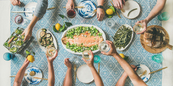 Mediterranean style dinner with cooked salmon and drinks wide composition