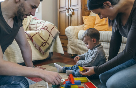 Parents playing with toddler a wooden game building