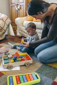 Mother playing with toddler a wooden game building