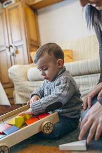 Toddler boy playing with a wooden game building