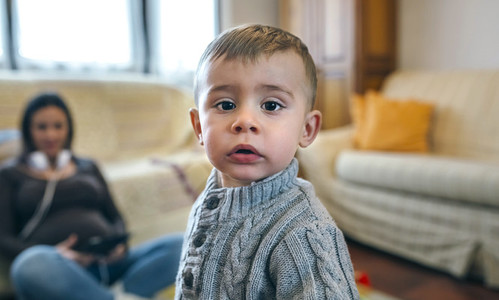 Little boy looking at camera with his pregnant mother sitting in background
