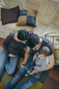 Family with child and pregnant mother looking tablet