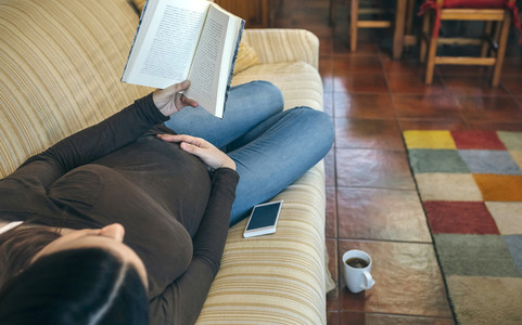 Pregnant reading a book lying on the couch