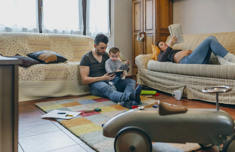 Father looking tablet with little son while the pregnant mother reads a magazine