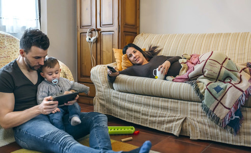 Father looking tablet with little son while the pregnant mother watches television