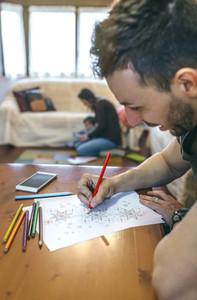 Young man coloring mandalas