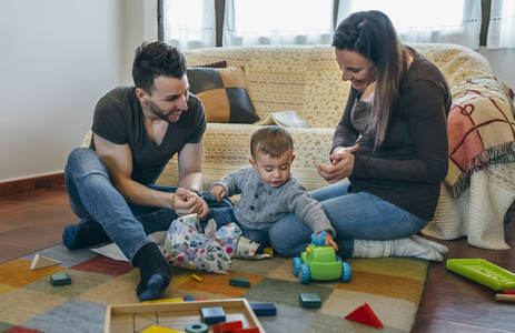 Parents with their little son opening a gift