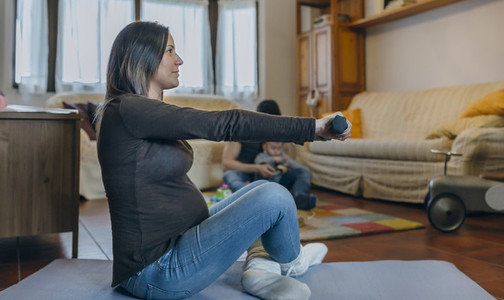 Pregnant woman exercising in the living room