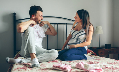 Man showing baby clothes to pregnant woman