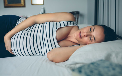 Pregnant woman sleeping in bed
