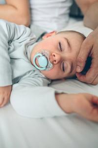 Baby asleep while parents caress