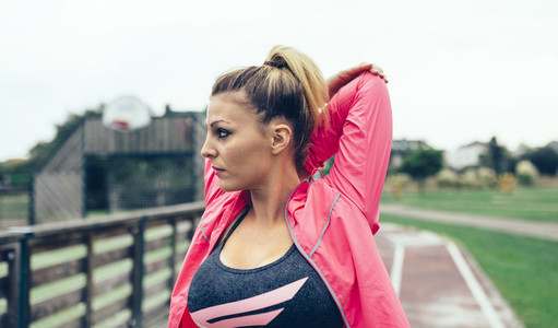 Young woman stretching arms before training outdoors