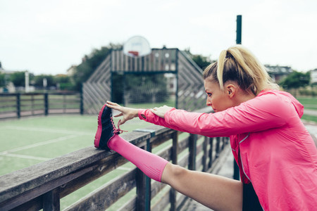 Young woman stretching legs before training outdoors