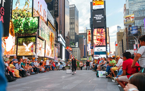 People looking street show in Times Square New York City USA