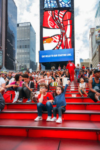 Kids sitting over famous stairs of Times Square  New York City  USA