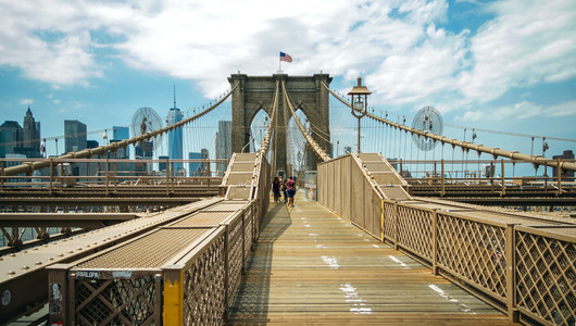 Pedestrians walking by Brooklyn Bridge in New York City
