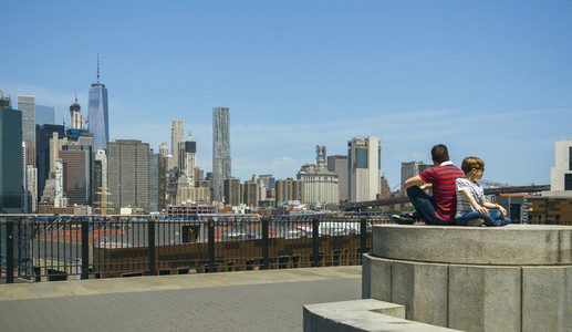 Man and boy sitting in front of Manhattan skyline  in New York C