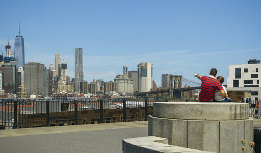 Man showing to kid the Manhattan skyline in New York City