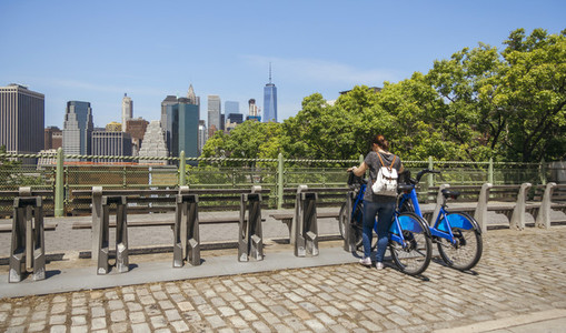 Woman taking a bike in front of Manhattan skyline in New York Ci