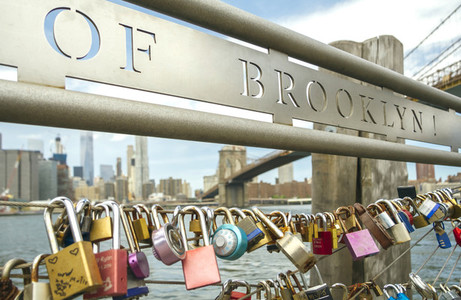 Love locks in fence with Brooklyn Bridge on background