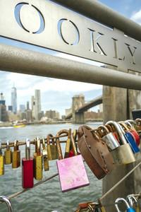 Love locks in fence with Brooklyn Bridge on background