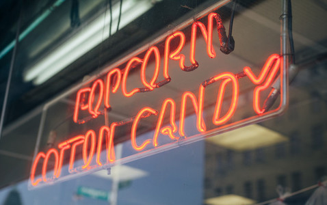 Red neon sign with words Popcorn Cotton Candy