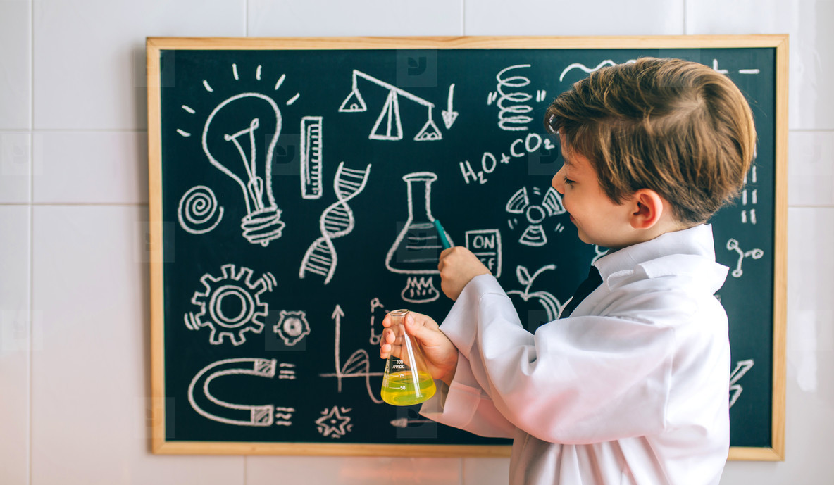 Boy dressed as chemist pointing at blackboard