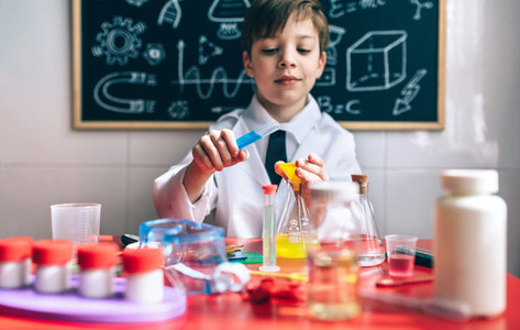 Serious little boy playing with chemical liquids