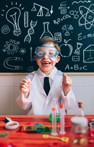 Happy kid with glasses laughing behind of experiments table