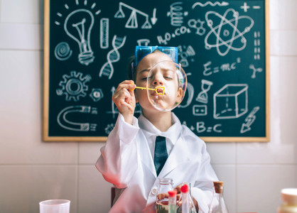 Kid doing soap bubbles against of drawn blackboard