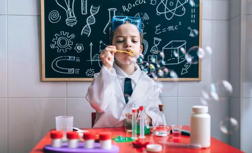 Kid doing soap bubbles against of drawn blackboard
