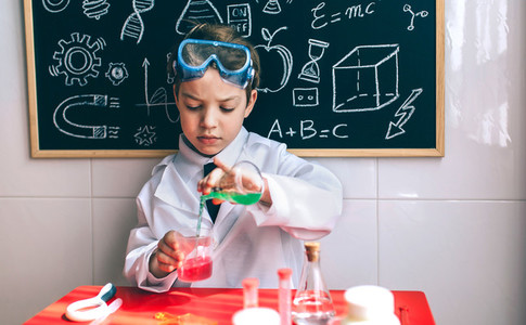 Serious kid playing with chemical liquids