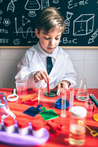 Kid playing to be chemist with colorful liquids