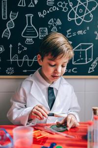 Happy kid looking liquid through magnifying glass