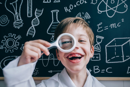 Happy kid looking at camera through magnifying glass