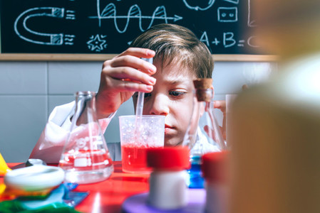 Kid playing with chemical liquids over table
