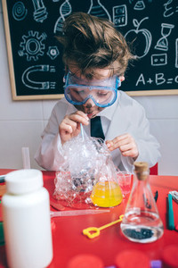 Kid doing soap bubbles with straw in glass