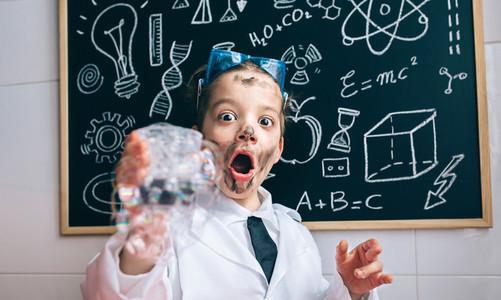 Happy little boy holding glass with soap foam