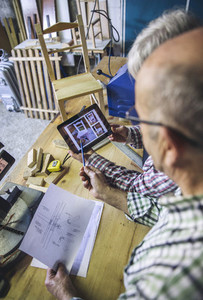 Senior couple in a carpentry looking tablet