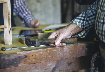 Carpenters hand holding a hammer
