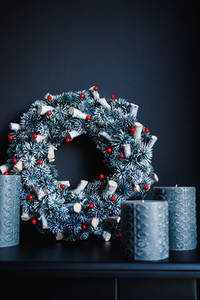 Grey candles and Christmas wreath on a decorative fireplace against black wall  Holidays decorations in a dark monochrome room interior