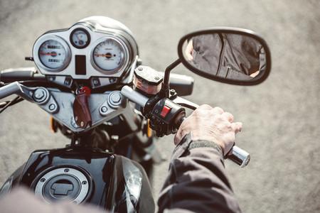 Senior man hand steering motorcycle on road