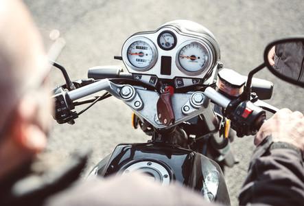 Senior man steering motorcycle on road