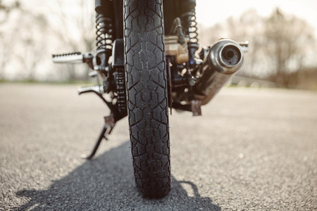 Wheel and exhaust pipe of motorcycle on road