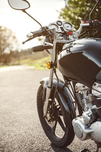 Black motorcycle on road over nature background