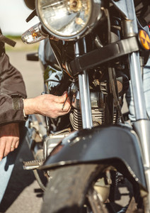 Senior man repairing damaged motorcycle engine