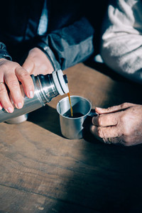 Senior couple hands pouring coffee from thermos