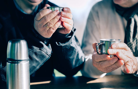 Senior couple hands holding cups with hot coffee